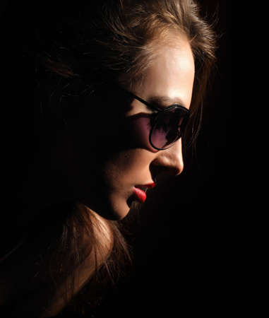 The beautiful woman in glasses on a black background Stock Photo