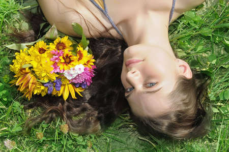 Portrait of the beautiful girl on a green grass with flowers