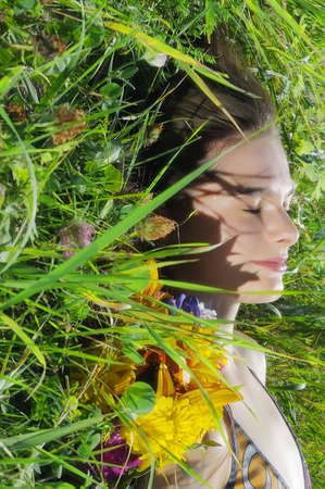 The beautiful woman sleeps in a grass