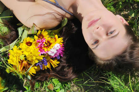 The beautiful woman lays in a grass with flowers