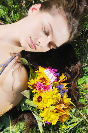 The beautiful woman with long hair sleeps on a grass Stock Photo