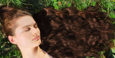 The beautiful woman with very long hair sleeps on a grass