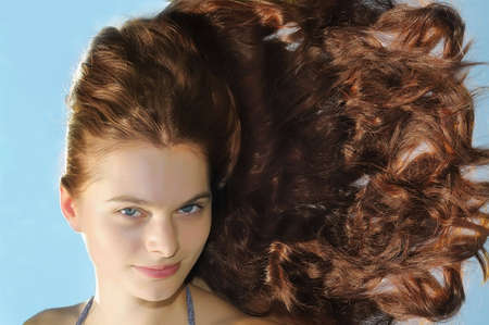 The beautiful woman with long hair on a blue background