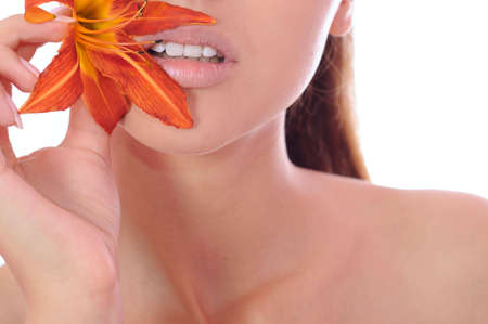 Beautiful lips of the young woman with a lily in hands