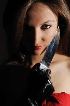 Young woman portrait staring at camera with a knife photo