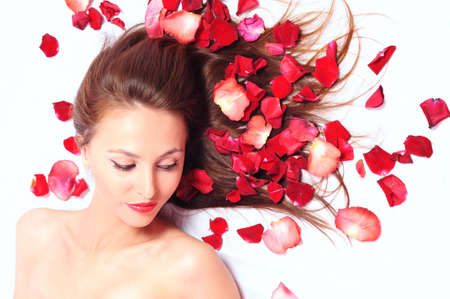 beautiful long-haired girl in petals of red roses