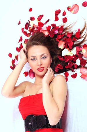 The woman in a red dress in rose-petals. It is not isolated photo