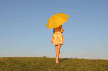 The harmonous woman in a yellow dress with an umbrella stands on a lawn against the sky
