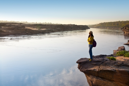 morn: Smiling woman standing on a mountain over a river  Stock Photo