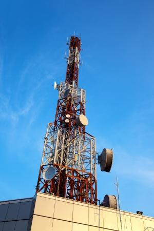 Red and white antenna (cellular tower) under blue sky. photo