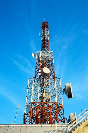 Red and white antenna  cellular tower  under blue sky  photo