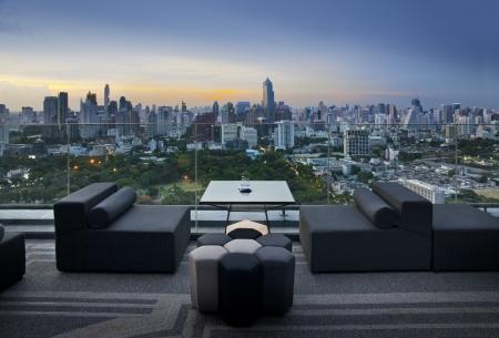 Sofa on terrace overlooking green park and building, Bangkok, Thailand