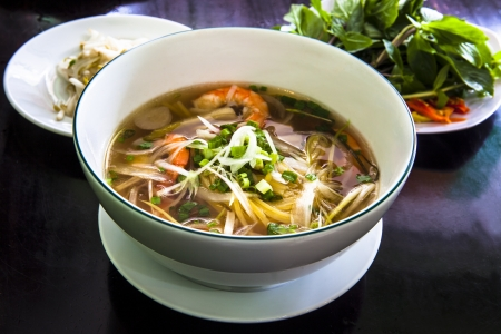 popular soup: Pho Vietnamese Rice Noodle Soup. Pho is a Vietnamese noodle soup consisting of broth, linguine-shaped rice noodles, a few herbs, and meat It is a popular street dish in Vietnam and the specialty of a number of restaurant chains around the world.  Stock Photo