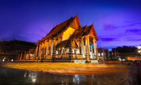 thep: Candle light from buddhists are moving around temple on full moon day, Bangkok,Thailand  Wat Suthat Thep Wararam was construction in 1807, and was submitted to UNESCO for consideration as a future World Heritage Site  Stock Photo