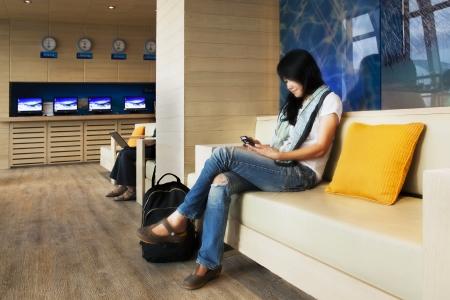 Belle voyageur avec un t�l�phone mobile � l'a�roport de voyageurs avec un t�l�phone mobile � l'a�roport de Suvarnabhumi, Bangkok, Tha�lande Banque d'images