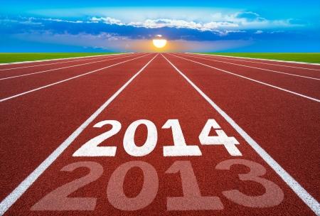 Nouvel An 2014 sur l'ex�cution concept de piste avec le soleil ciel bleu Nouvel An, en commen�ant, la concurrence et le concept de but, nombre blanc sur la nouvelle piste de course avec l'herbe verte et de ciel bleu Banque d'images
