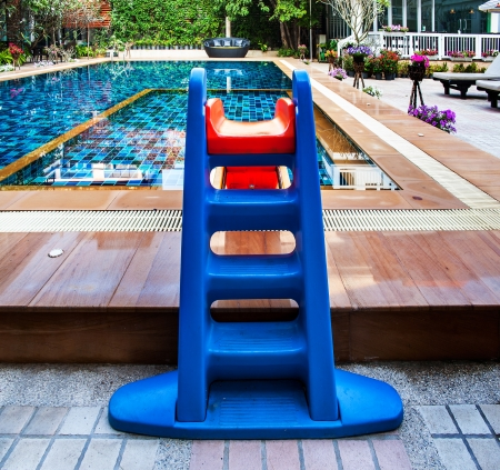 slide glass: Beautiful swimming pool with tot slide  Colorful tot slide in swimming pool with chairs, umbrellas, sofa and flowers
