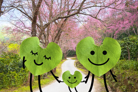 Happy family holding hands  environmental protection concept  Green leaf in heart shape with road, sakura and green trees  photo