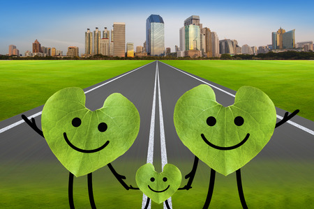 Happy family on the green road with city  environmental protection concept  Green leaf in heart shape on the green road  photo