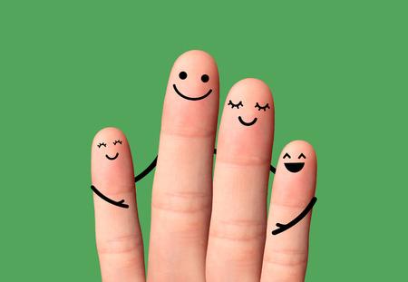 Abrazo feliz de la familia en fondo verde Dedos felices, Dos pequeños niños, el padre y la madre