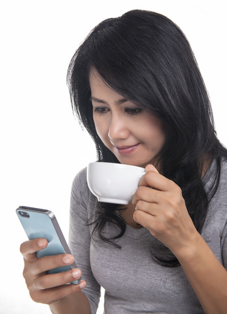 Beautiful woman texting on her mobile phone and drinking a coffee   photo