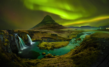 Aurora at Kirkjufell and Waterfall Kirkjufellsfoss, Landmark of Iceland. Kirkjufell Church mountain is mountain on the north coast of Icelands Snfellsnes peninsula.