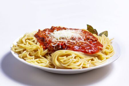 Delicious Spaguetti Pasta with bolognesa tomato sauce and chopped meat. Adorned with cheese and Laurel leaf
