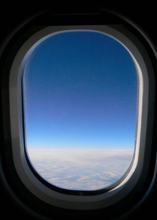 onto: View from aeroplane window onto cloud & blue sky. Stock Photo