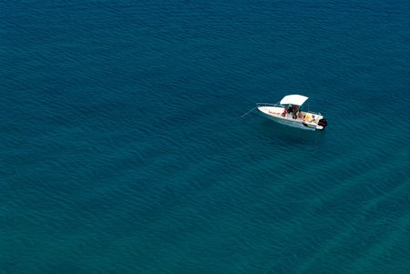 Small day boat anchored in shallow waters. Stock Photo - 575280