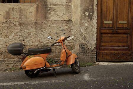 vespa piaggio: arancione scooter parcheggiati in stretta vecchia strada di Roma  Archivio Fotografico