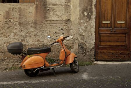 vespa: orange scooter parked in narrow old street of rome