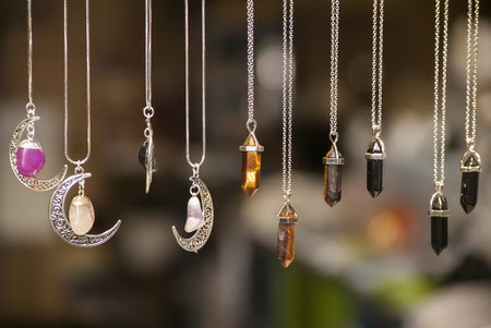Miscellaneous silver necklaces of various shapes and colors set with colored stones on blurred background.