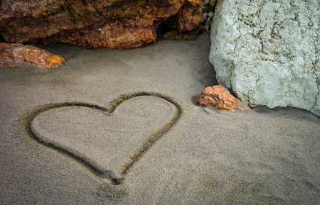 A heart drawn on the sand of the unspoiled beach: a gesture of sweet and poetic love for those who truly love