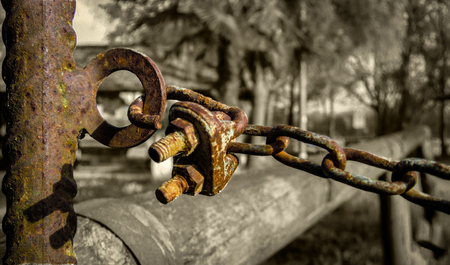 Detail of a rusty chain and a padlock and corroded by time in a situation with low very bleak and gloomy lighting.