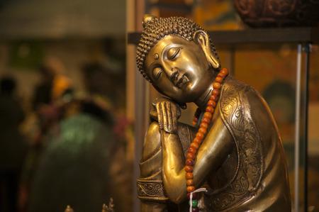 Spiritual Bronze statuette of a small buddha, spiritual figure in a stall at a trade fair.