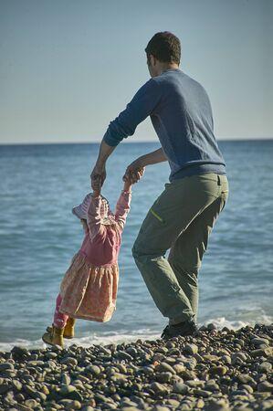 Vader en dochter zijn van plan samen en liefdevol aan de kust van de zee te spelen. Kinder herinneringen en herinneringen Stockfoto