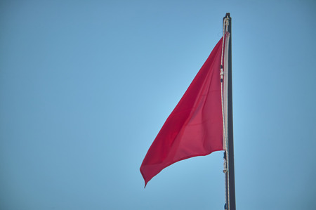 Pole with raised red flag, symbol of danger for bathers and navigators. Imagens