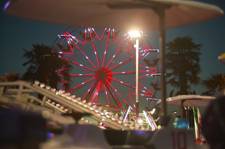 View of a panoramic wheel with the sunset behind, taken in a luna park in a seaside resort. Stock Photo