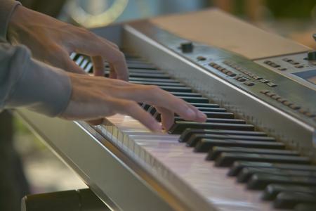 Hand van een musicus die de sleutels van een elektronisch toetsenbord drukt terwijl het spelen bij een overleg