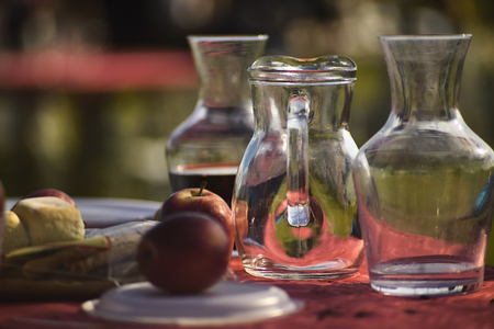A table set in a Venetian tavern, featuring wine glasses, apples and breads in the foreground, all ready to serve lunch. Image with a predominant red color contrasting with the transparency of the glass of the carafe.