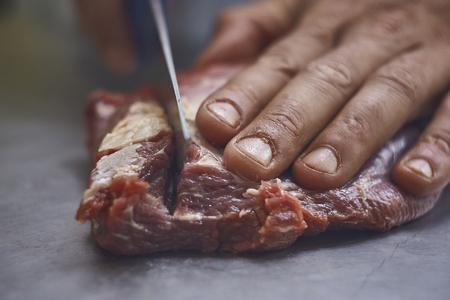 detail van de hand van een slager die van plan is om een ??stuk vlees met het mes te snijden, waarvan je de vezels en textuur heel goed opmerkt,