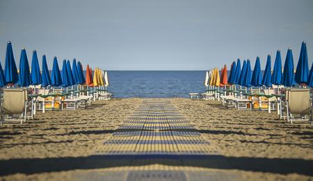 イタリアのリニャーノ・サビア・ドーロの傘とラウンジャーを持つビーチの完全にスペキュラで対称的な眺め。海にしかできない穏やかで平和な気