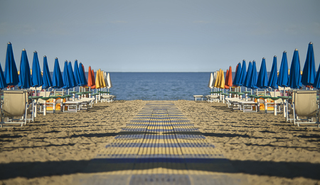 Perfect spiegelende en symmetrische weergave van het strand met parasols en ligstoelen van Lignano sabbia d'oro in Italië. Een scène verstoken van mensen die emoties van rust en vrede geven zoals alleen de zee dat kan.