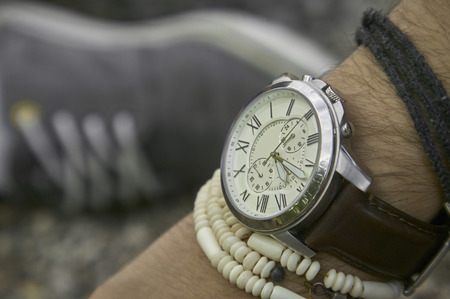 Detail of a vintage wristwatch worn by a boy with other bracelets, symbol of time passing. A great acession for a perfect outfit. Reklamní fotografie - 88900285