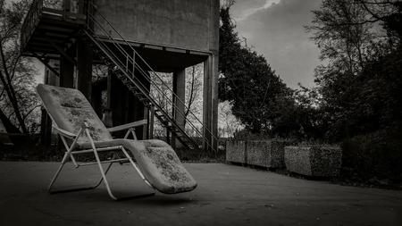Compositie met een oude ligstoel op een verlaten plek met een heel saai en somber uiterlijk: een horrorfilmscenario. Stockfoto