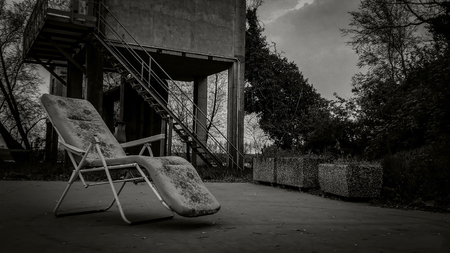 Composition with an old deck chair in an abandoned place with a very dull and gloomy appearance: a horror movie scenario.