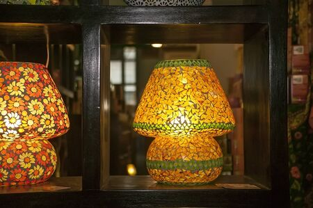 Lamp made of yellow glass pieces for a hot lizard, leaning on a dark wooden bookcase: tastefully decorated.
