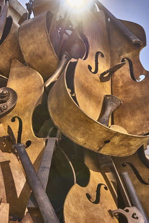 Old vintage violins are now reduced to pieces and packed in a unique pile. Vertical Shot.