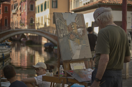 Painter painting a Venice scene live with him the way he is living alive of people and tourists who pass. Banco de Imagens - 90640661