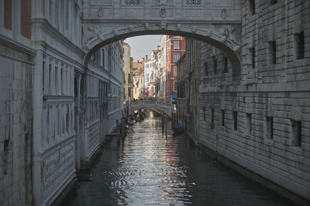 Small water course in Venice surrounded by highly decorated historic buildings and houses that draw the skyline at the bottom.